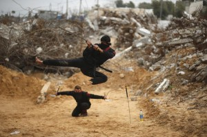 Palestinian youth jumps with a sword as he demonstrates his ninja-style skills for the photographer in front of the ruins of buildings, that were destroyed in 2014 war, in the northern Gaza Strip